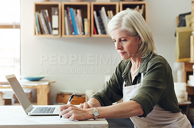 Buy stock photo Shot of a mature woman writing notes while using a laptop in a pottery studio