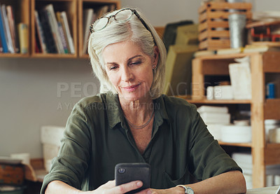 Buy stock photo Shot of a mature woman using a cellphone while working in a pottery studio