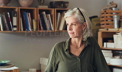 Buy stock photo Shot of a mature woman looking thoughtful while working in a pottery studio