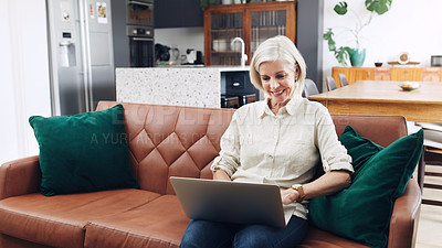 Buy stock photo Cropped shot of an attractive mature woman sitting alone on her sofa and using her laptop at home