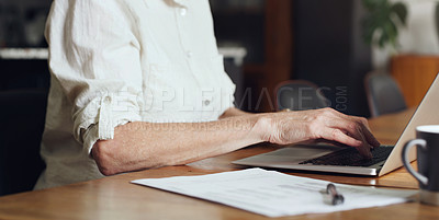 Buy stock photo Cropped shot of an unrecognizable woman sitting alone at home and using a laptop to go through her finances