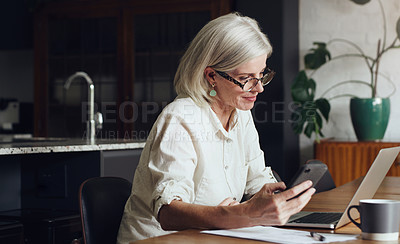 Buy stock photo Cropped shot of an attractive mature woman sitting alone and using a laptop and cellphone at home