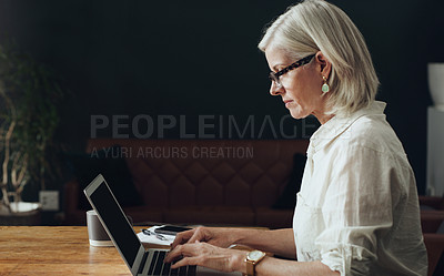 Buy stock photo Cropped shot of an attractive mature woman sitting alone and using her laptop at home
