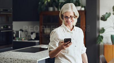Buy stock photo Cropped shot of an attractive mature woman standing alone and using her cellphone at home