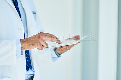 Buy stock photo Closeup shot of an unrecognisable doctor using a digital tablet in a lab