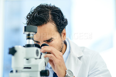 Buy stock photo Shot of a young scientist using a microscope in a lab