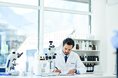 Buy stock photo Shot of a young scientist writing notes in a lab