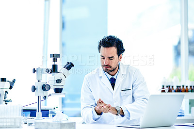 Buy stock photo Shot of a young scientist using hand sanitiser while working in a lab