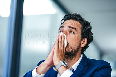 Buy stock photo Shot of a young businessman blowing his nose with a tissue at his desk in a modern office