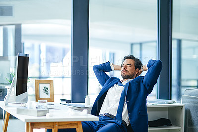 Buy stock photo Shot of a young businessman relaxing at his desk in a modern office