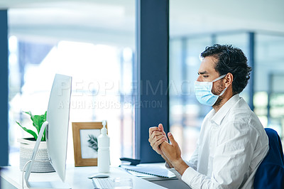 Buy stock photo Shot of a young businessman using hand sanitiser while suffering from flu at his work desk