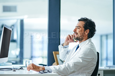Buy stock photo Shot of a young doctor using a smartphone and computer while working at his desk