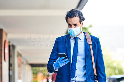 Buy stock photo Shot of a young businessman wearing a mask and using a smartphone while walking through the city