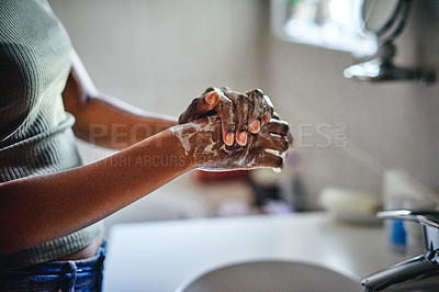Buy stock photo Cropped shot of an unrecognizable woman washing her hands in her bathroom basin at home