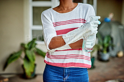 Buy stock photo Cropped shot of an unrecognizable woman holding a cleaning detergent while standing in her kitchen at home