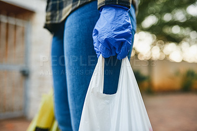 Buy stock photo Cropped shot of an unrecognizable woman holding plastic bags full of groceries outside her house during the day