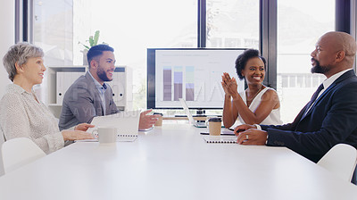 Buy stock photo Cropped shot of a diverse group of businesspeople sitting together and having a meeting in the office during the day