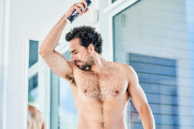 Buy stock photo Cropped shot of a handsome young man spraying deodorant to his armpit in the bathroom at home