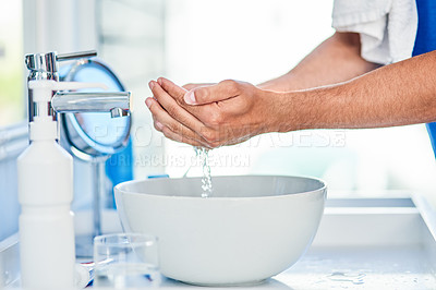 Buy stock photo Cropped shot of an unrecognizable man washing his hands inside his bathroom at home