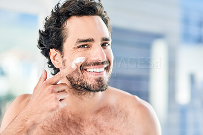Buy stock photo Cropped shot of a handsome young man applying moisturizer to his face inside the bathroom at home