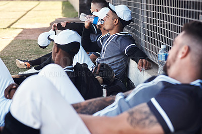 Buy stock photo Shot of a young man drinking water and watching a baseball game with his team mates