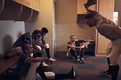 Buy stock photo Shot of a young man yelling at his fellow baseball players in a locker room.