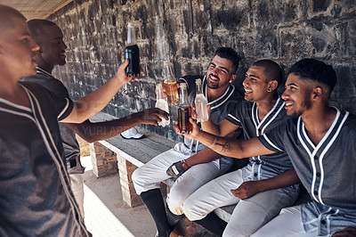 Buy stock photo Shot of a group of young men celebrating with drinks after playing a baseball game