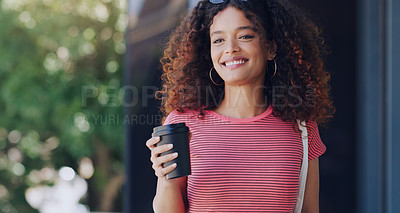 Buy stock photo Cropped shot of a young woman holding a takeout coffee while walking through the city