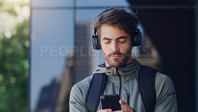 Buy stock photo Shot of a man walking outside wearing headphones and using his cellphone