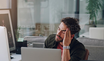 Buy stock photo Cropped shot of a handsome young businessman looking stressed while working in his office