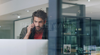 Buy stock photo Cropped shot of a handsome young businessman making a phonecall while working on his computer in the office