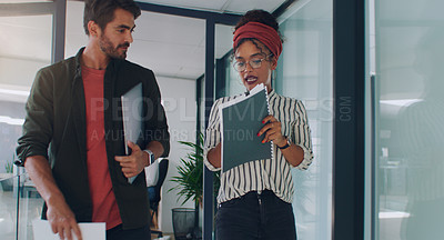 Buy stock photo Cropped shot of two young businesspeople going over paperwork while walking through their office