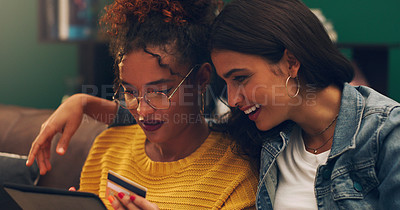 Buy stock photo Shot of two friends browsing online while using a credit card