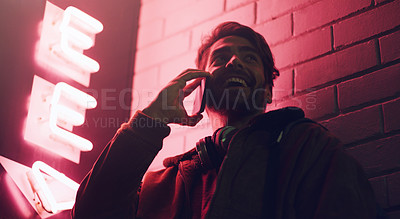 Buy stock photo Shot of a young man talking on his cellphone while standing outside a building