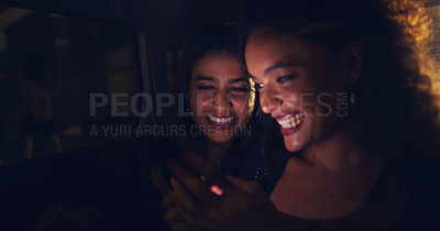 Buy stock photo Shot of two women looking at something on a cellphone while sitting in a car