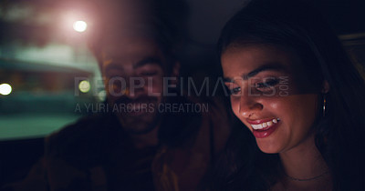 Buy stock photo Shot of a young couple looking at something on a screen while sitting in a car