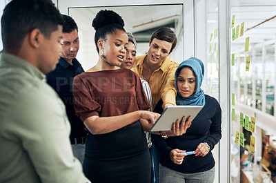 Buy stock photo Shot of a group of businesspeople using a digital tablet while brainstorming with notes on a glass wall in an office