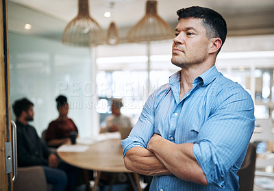 Buy stock photo Shot of a mature businessman standing in an office with his colleagues in the background