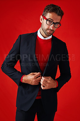 Buy stock photo Studio portrait of a handsome and stylish young man buttoning his blazer against a red background