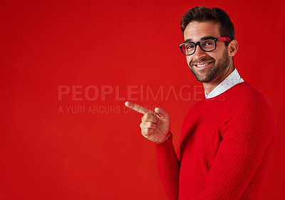 Buy stock photo Studio portrait of a handsome and stylish young man pointing towards copyspace against a red background