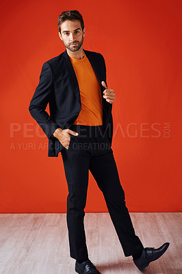 Buy stock photo Studio portrait of a handsome and stylish young man posing with his hand in his pocket against a red background