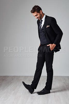 Buy stock photo Studio shot of a handsome and stylish young man posing with his hands in his pockets against a grey background