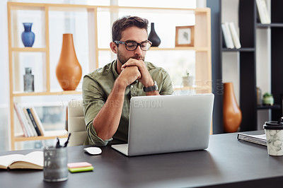 Buy stock photo Cropped shot of a handsome young businessman working on his laptop in the office