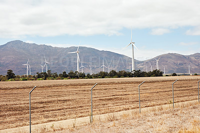 Buy stock photo Shot of wind turbines out on an open field