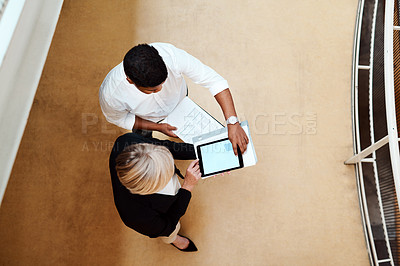 Buy stock photo High angle shot of two businesspeople using a digital tablet together in an office