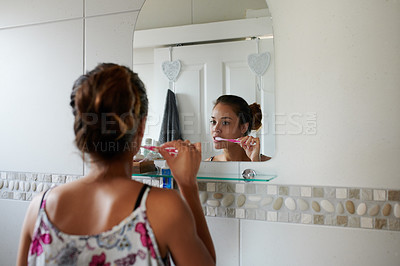 Buy stock photo Shot of a young woman brushing her teeth in the bathroom at home