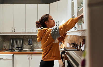 Buy stock photo Shot of a young woman busy in the kitchen at home
