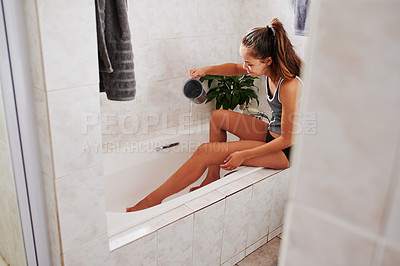 Buy stock photo Shot of a young woman pouring water on her legs in the bathtub at home