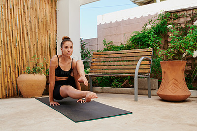 Buy stock photo Shot of a fit young woman doing yoga at home