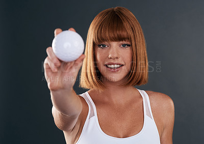 Buy stock photo Shot of a sporty young woman posing with a ball against a grey background